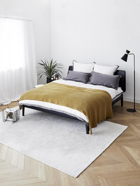 Designer Schlafzimmer Ein cleanes schwarzes Bett mit Stehleuchte, Beistelltisch und einem hellen Teppich