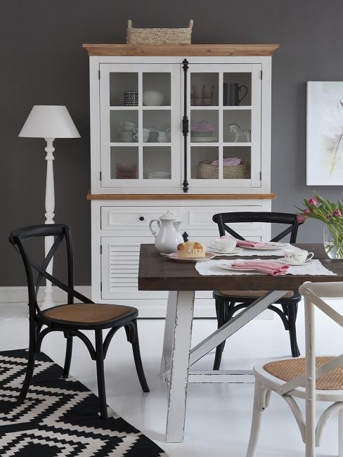 Kleines Esszimmer einrichten mit schwarz-weißen Stühlen, Tisch, Teppich und Vitrine