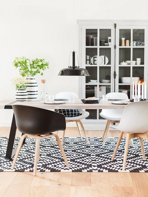 Helle Tischtafel auf schwarz-weißem Muster-Teppich