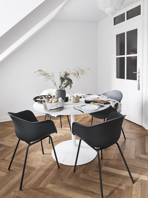 Kleines Esszimmer einrichten im gesonderten Raum mit weißen, rundem Tisch und schwarzen Stühlen