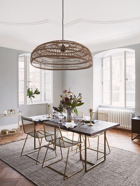 Rechteckiger Tisch auf einem Teppich mit XL Lampe darüber im Wohn Esszimmer