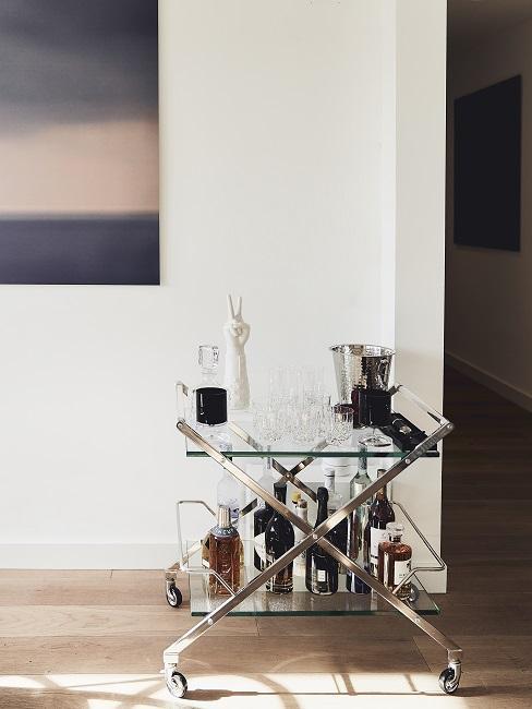 EIn Barwagen mit Deko, Gläsern und Flaschen an der Wand mit einem puristischen Wandbild stehend