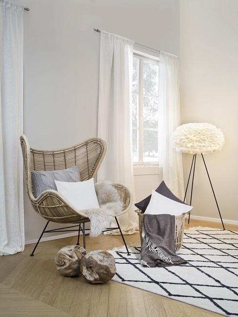 Helles Landhaus-Schlafzimmer mit Rattan-Sessel, einem schwarz-weißen Teppich und einer hellen Federlampe