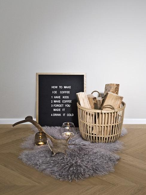 Ein graues Lammfell mit einem Korb mit Kaminholz, Kerzen und einer Buchstabentafel mit Holzrahmen