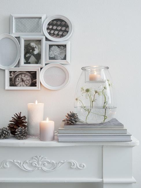 Kaminsims mit reichlich Kerzen und Tannenzapfen Deko, darüber ein Bilderrahmen