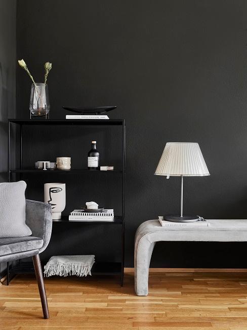 Ein Zimmer mit schwarzen Wänden, davor ein schwarzes Metallregal mit moderner Deko, eine Sitzbank mit Tischlampe und ein hellgrauer Samtstuhl