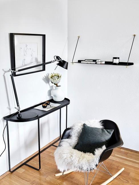 Eine schwarze Wandkonsole im minimalistischen Stil als Schreibtisch genutzt, davor ein moderner Schaukelstuhl mit Fell und Kissen