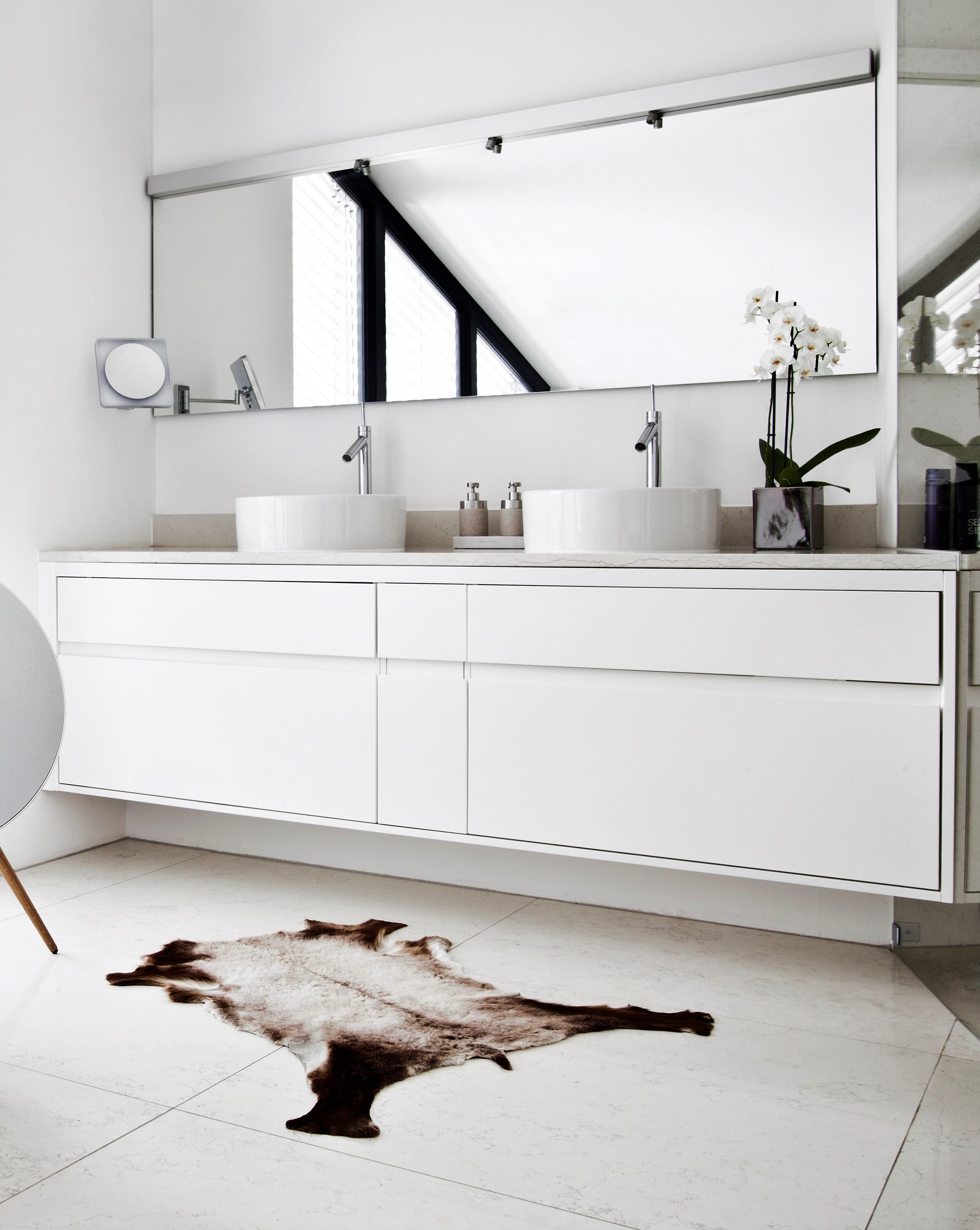 Ein weißes modernes Bad im puristischen Stil mit einer Orchidee und einem Fell auf dem Boden als Deko