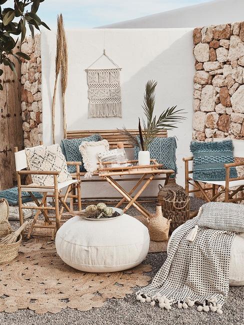 Ein Outdoor Bereich mit Bambusmöbeln, vielen Deko Kissen im Boheian Style sowie Decken, einem Jute Teppich und einem Wand Makramé