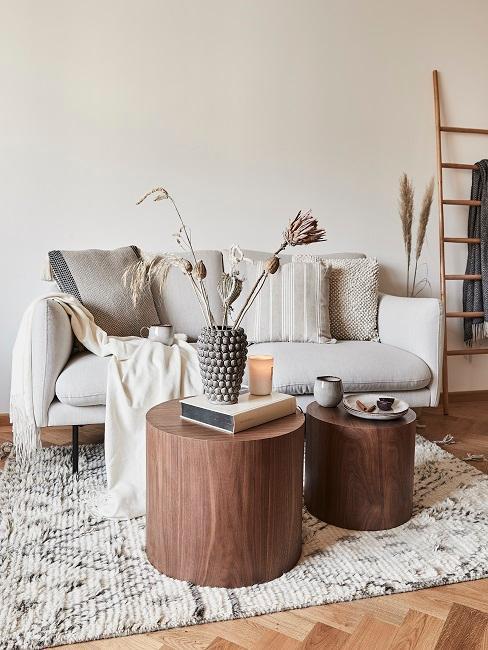 Ein helles Sofa mit Kissen, einem Plaid, vor zwei runden Holz Couchtischen mit Deko und einem Bohemian-Muster-Teppich