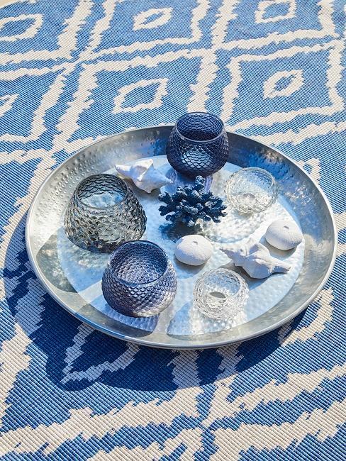 Blau-weißer Boho Teppich für outdoor im Ibiza Style, darauf ein Silber-Tablett mit Kerzen und Muscheldeko