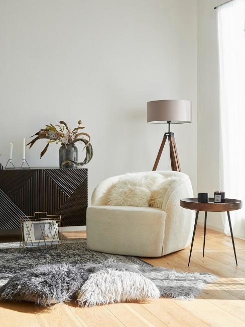 Wohnzimmer Ecke mit einem hellen Sessel mit Kuschelkissen, einer Stehlampe, einem Beistelltisch und einem Sideboard, davor ein Lammfell-Teppich