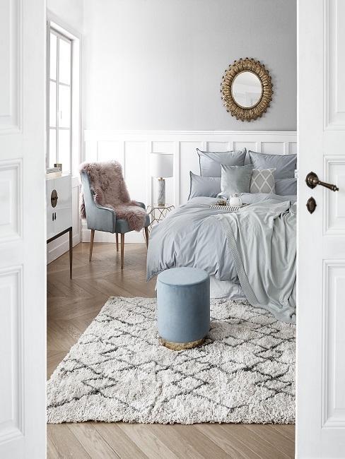 Helles Luxus-Schlafzimmer mit einem großen Bett, einem Muster-Teppich, einem Samtstuhl mit Fell und einem Samt-Pouf