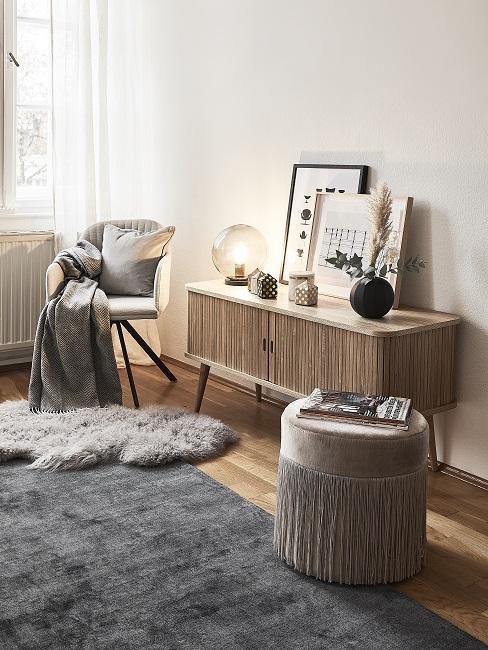 Zimmer mit einem Holz-Sideboard, einem grauen Teppich und einem edlen Samt-Pouf mit Fransen