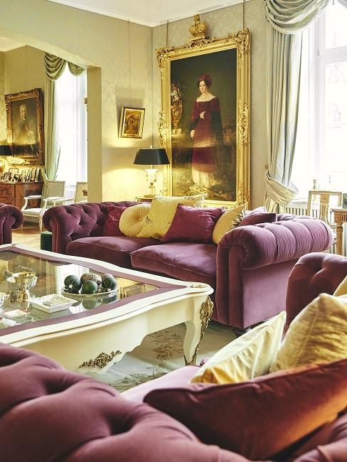 Barockes, luxuriöses Wohnzimmer mit dunkelroter Polstergarnitur und opulenter Deko