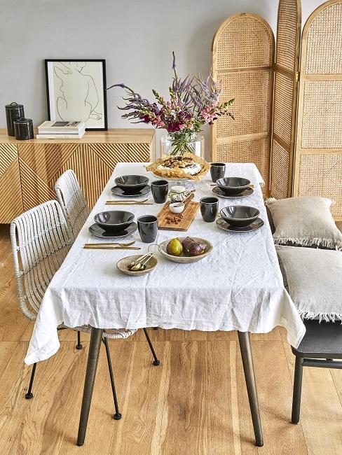 Gedeckter Esstisch mit einer Tischdecke sowie einer Sitzbank