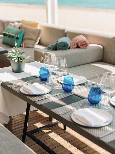 Gedeckter Tisch mit blauen Gäsern in einem Beachclub am Strand, auf der Bank bunte Ibiza Style Dekokissen