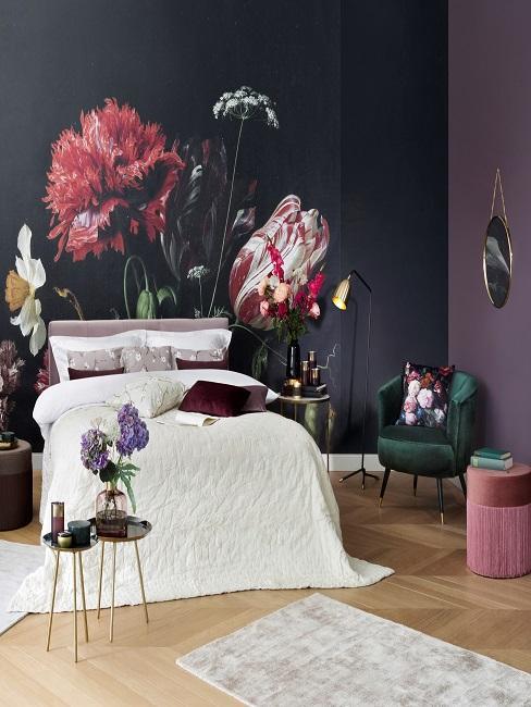 Schlafzimmer mit einer floralen Tapete an der Wand hinter dem Bettkopf, die seitlichen Wände sind in Violett gestrichen