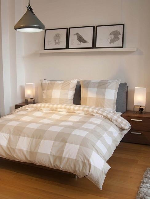Schlafzimmer mit Wandbildern über Doppelbett mit karierter Bettdecke