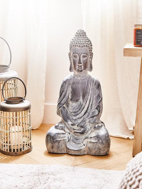 Laternen neben großer Buddha Figur im Bad
