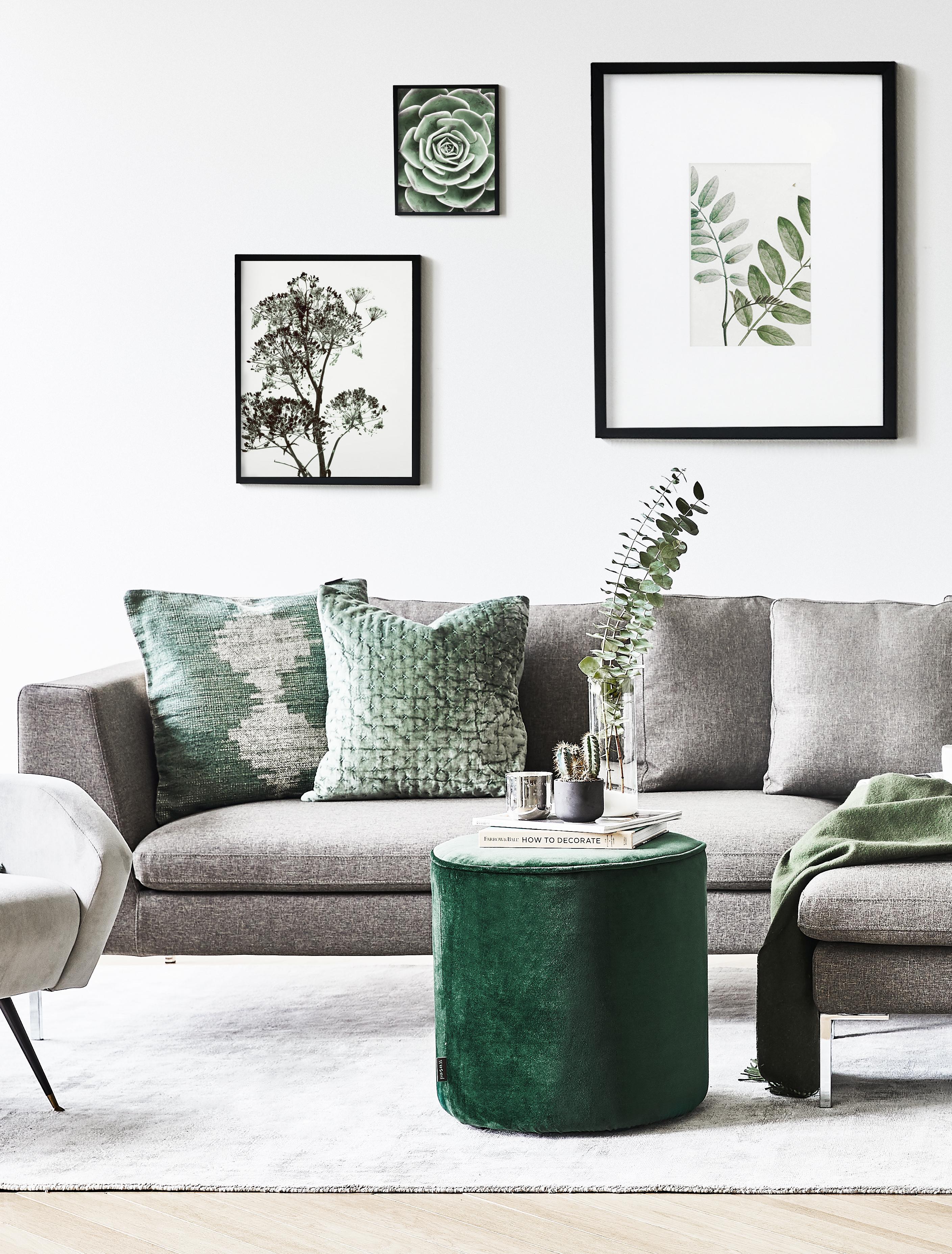 Sofa in einem Wohnzimmer im Mix mit grünen Accessoires und Wandbildern mit Naturmotiven zur Gemütlichkeit