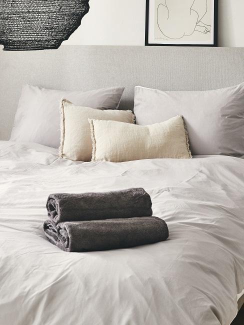 Bett in Hellgrau mit weißer Leinen-Bettwäsche und Handtüchern am Bettende