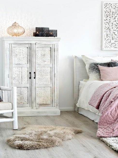 Schlafzimmer in Weiß- und Rosatönen mit verschnörkeltem Shabby Schrank aus Holz, einem Fell-Teppich und einem weißen Holzbett