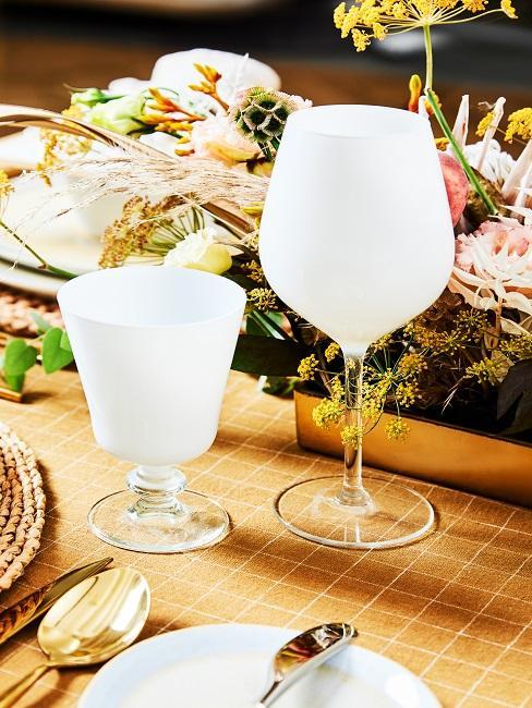 Weiße Gläser auf dem Tisch vor Blumendeko