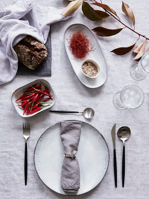 Grau gedeckter Tisch mit Brot und Gewürzen