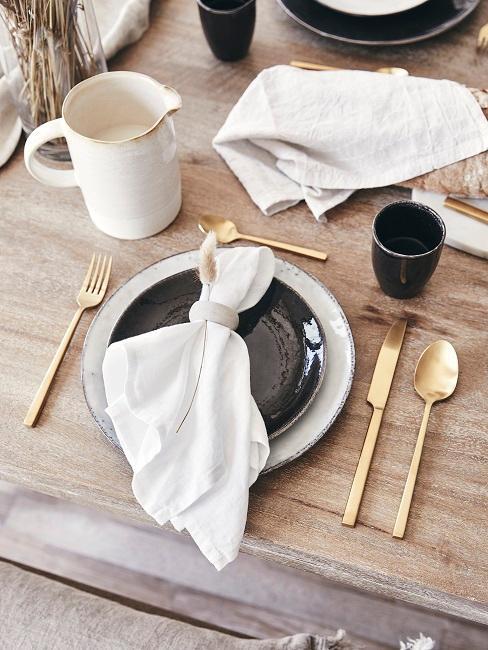 Holztisch mit Tischgedeck in Schwarz, Weiß und Gold