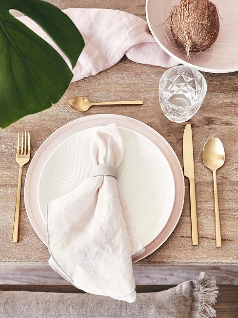 Tischgedeck auf einem Holztisch mit goldenem Besteck