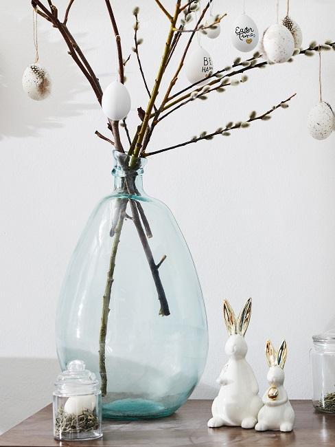 Große Vase mit Osterzweigen neben weiß-goldenen Osterhasen
