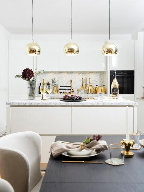 Die Küche von Novalanalove mit Essbereich, einem dunklen Holztisch zu hellen Samtstühlen, im Hintergrund drei goldfarbene Pendelleuchten über dem Küchentresen
