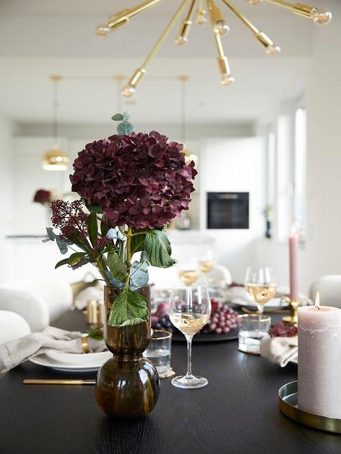 Der gedeckte Esstisch aus dunklem Holz mit frischer Blume in einer Vase und Kerzen, im Hintergund die Küche von Novalanalove