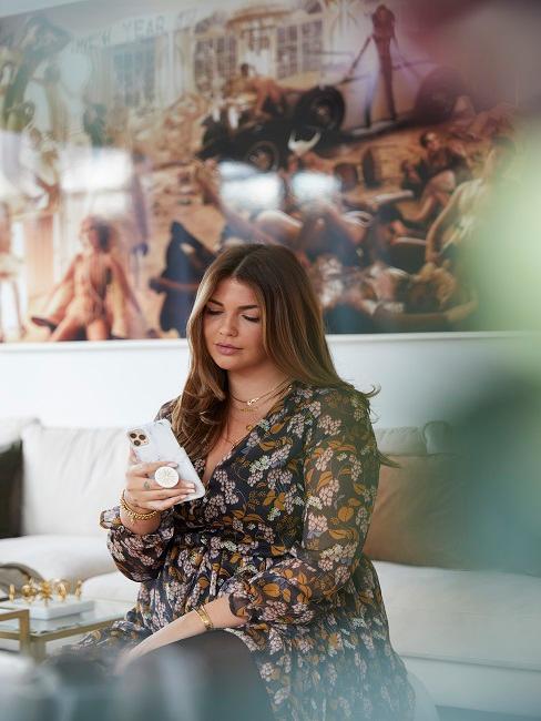 Novalanalove auf ihrem Sofa sitzend mit dem Handy in der Hand