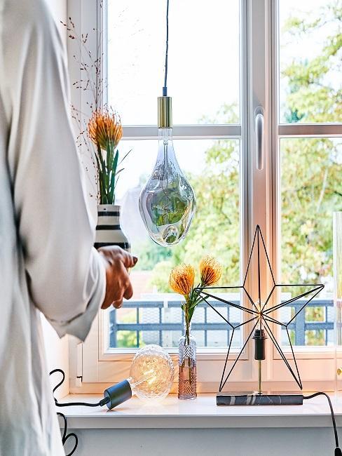 Fenster mit dekorativen Leuchten und Vasen