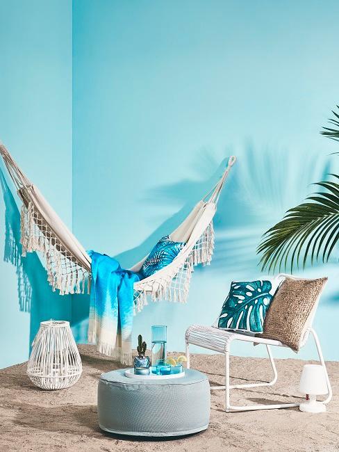 Balkon mit türkisfarbenen Wänden, Teppich, einer Hängematte sowie weiterer Deko wie Kissen und einem Windlicht