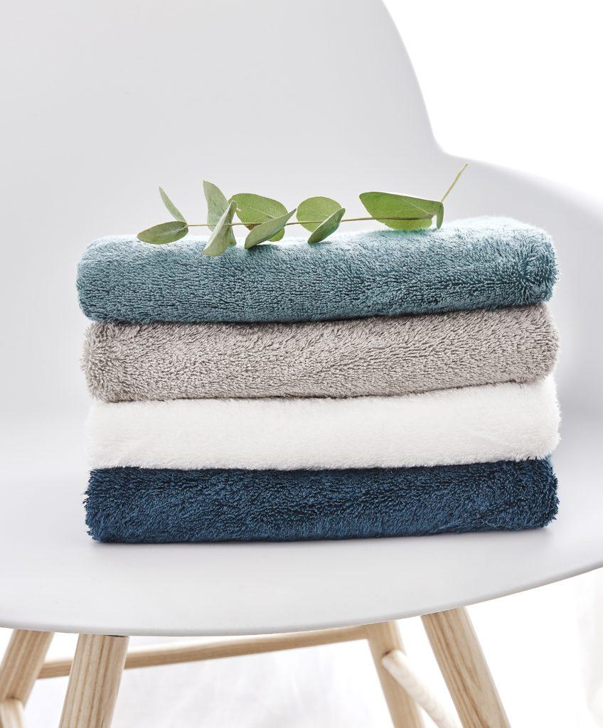 Gefaltete Handtücher auf einem Hocker