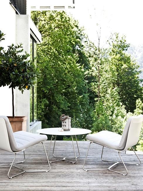 Luxus Terrasse mit Holz-Boden und einem Design Tisch sowie zwei passenden Design Stühlen