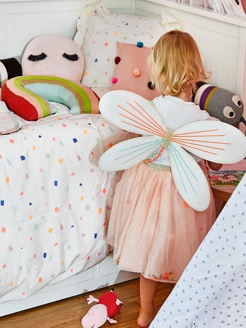 Mädchen mit Feen-Flügeln auf dem Rücken vor ihrem Bett mit vielen bunten Textilien und Deko Accessoires