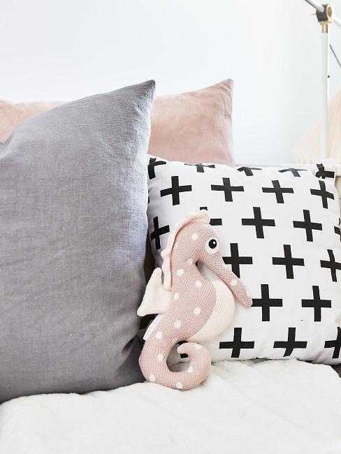 Bett mit vielen Kissen sowie einem Seepferdchen Kuscheltier