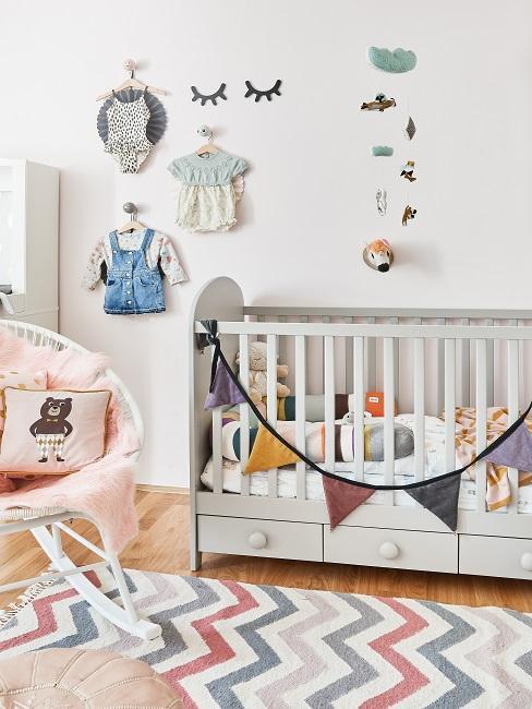 Kinderzimmer mit Gitterbett, einem bunten Teppich, viel Deko sowie Garderobenhaken mit dekorativer Kleidung an der Wand