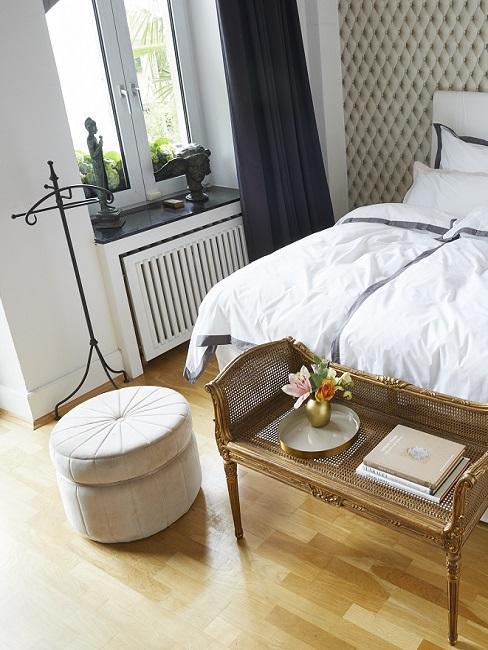 Designer Schlafzimmer mit goldener Bank und hellem Pouf