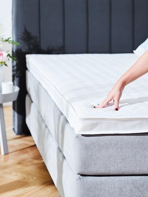 Hand berührt Matratze auf Bett