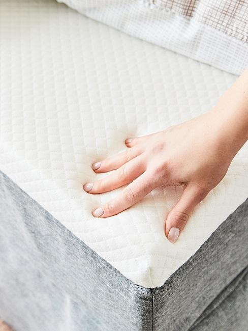 Hand berührt Matratze