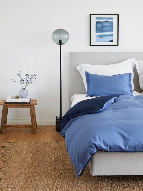 Maritimes Schlafzimmer mit blauer Bettwäsche und Juteteppich