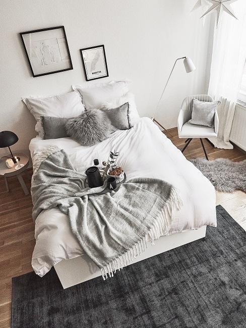 Scandi Schlafzimmer mit schwarzem Teppich und grauen Kissen