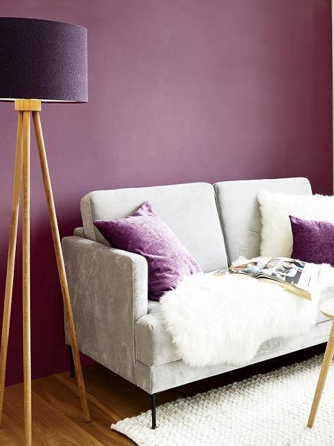 Warme Wandfarbe Lila hinter weißem Sofa