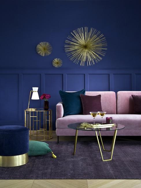 Dunkelblaue Wohnzimmerwand mit rosa Sofa und golderner Wanddeko
