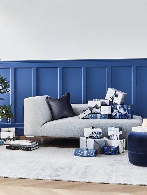 Blaue Wandvertäfelung mit grauer Couch und dunkelblauen Accessoires
